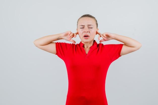 Młoda kobieta zatykająca uszy palcami w czerwonej koszulce i wyglądająca na zirytowaną