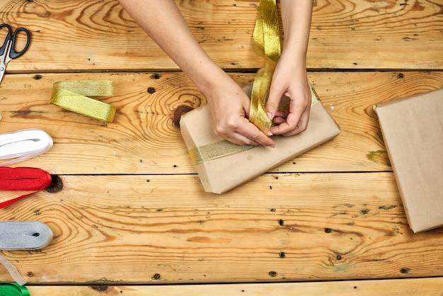 Młoda kobieta, zawijając prezent gwiazdkowy. twórz prezenty świąteczne. diy prezenty świąteczne dla przyjaciół i rodziny