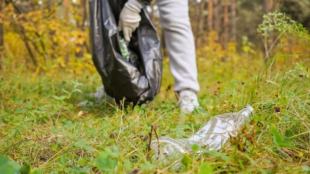 Młoda kobieta zbiera śmieci w czarnym opakowaniu w lesie