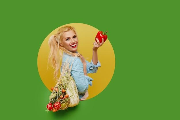 Młoda kobieta zbierała świeże warzywa w torbie strunowej na zielonym tle. wygląda z okrągłej dziury w ścianie.