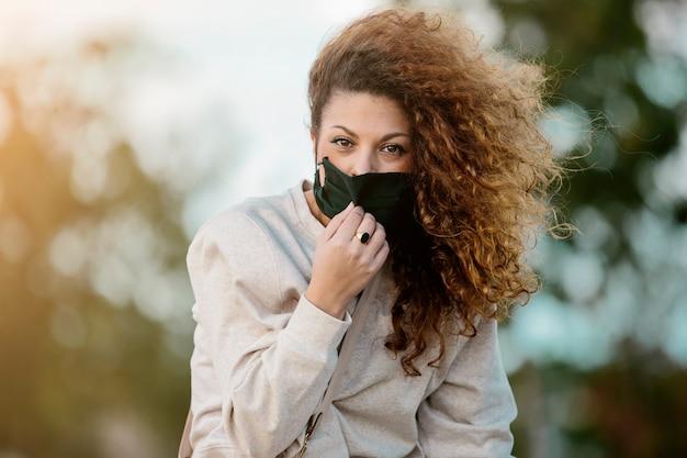 Młoda kobieta zdejmując maskę, patrząc prosto w kamerę na wsi. koncepcja stylu życia koronawirusa.