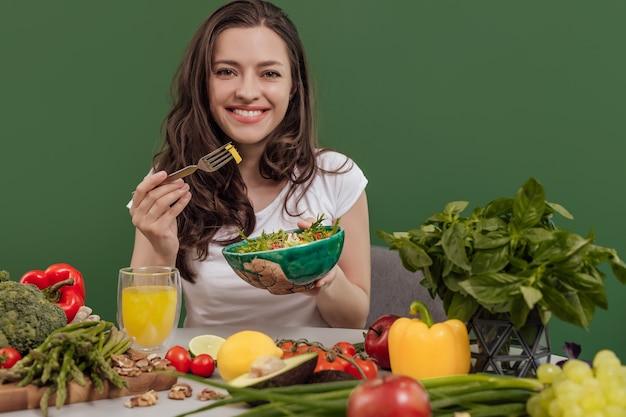 Młoda kobieta zdrowej żywności na zielonym tle