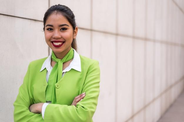 Młoda kobieta zdziwiona lub załoga uśmiecha się skrzyżowanymi rękami na zielono