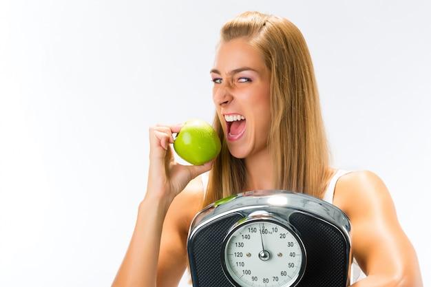 Młoda kobieta ze skalą pod pachą i jabłko