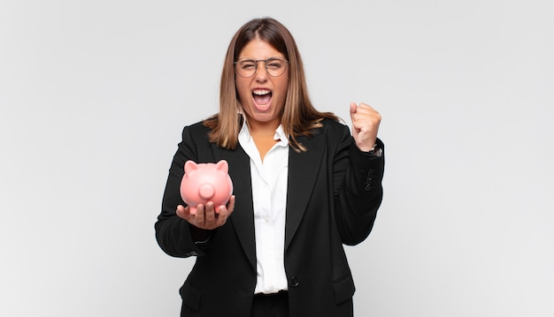 Młoda kobieta ze skarbonką krzycząca agresywnie z gniewnym wyrazem twarzy lub zaciśniętymi pięściami świętująca sukces