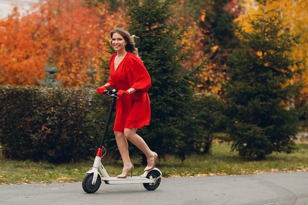 Młoda kobieta ze skuterem elektrycznym w czerwonej sukience w parku jesienią