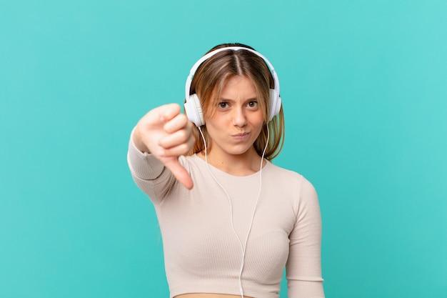 Młoda kobieta ze słuchawkami czuje krzyż, pokazując kciuk w dół