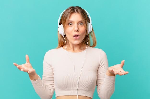 Młoda kobieta ze słuchawkami czuje się bardzo zszokowana i zaskoczona