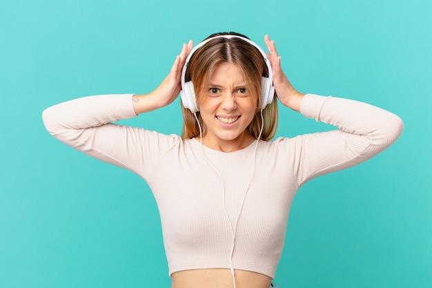 Młoda kobieta ze słuchawkami czuje się zestresowana, niespokojna lub przestraszona, z rękami na głowie