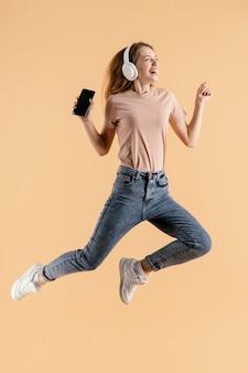 Młoda kobieta ze słuchawkami i mobilnym skokiem