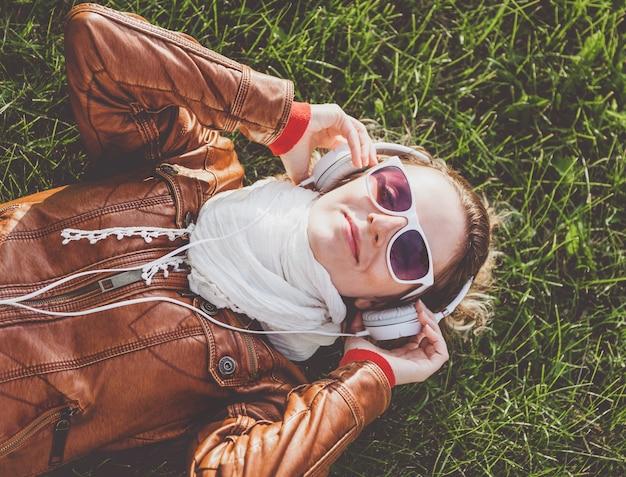 Młoda kobieta ze słuchawkami leży na trawie