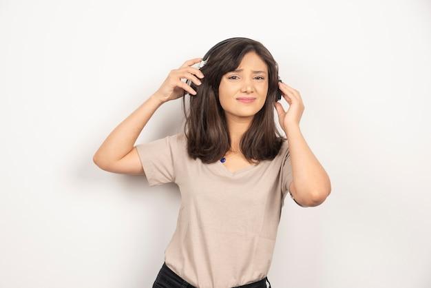 Młoda kobieta ze słuchawkami na białym tle.