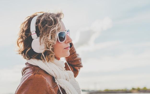Młoda kobieta ze słuchawkami na tle nieba