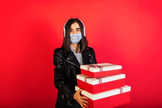 Młoda kobieta ze słuchawkami nosi maskę medyczną i trzyma pudełka na prezentach na czerwonej ścianie