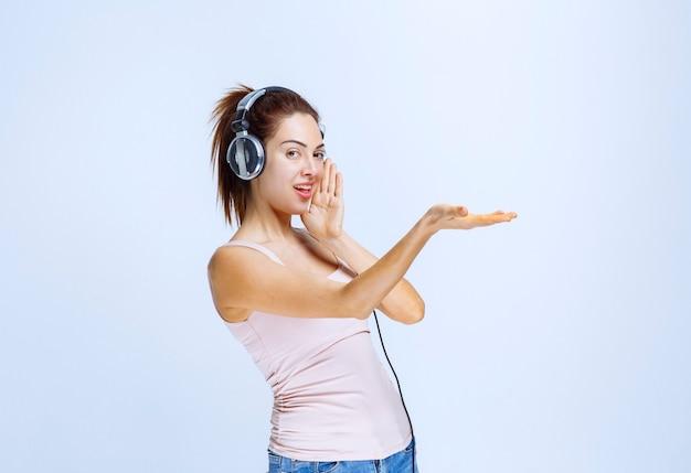 Młoda kobieta ze słuchawkami prezentuje coś po prawej stronie