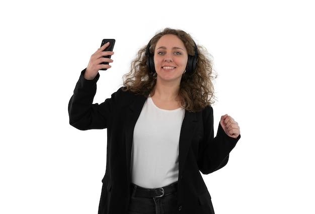Młoda kobieta ze słuchawkami taniec, trzymając telefon komórkowy ręką na białym tle