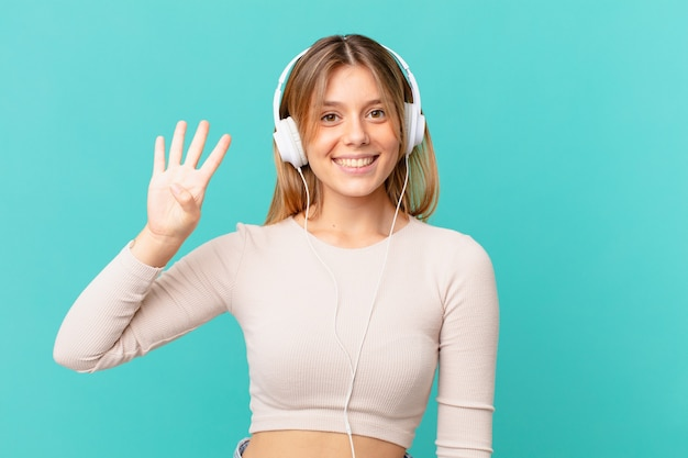 Młoda kobieta ze słuchawkami uśmiecha się i wygląda przyjaźnie, pokazując cyfrę cztery