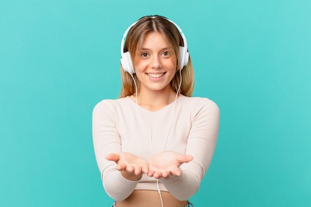 Młoda kobieta ze słuchawkami uśmiecha się radośnie z przyjaznym, oferującym i pokazującym koncepcję