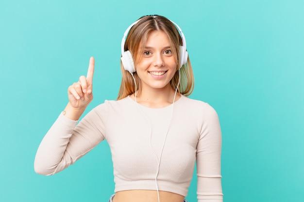 Młoda kobieta ze słuchawkami uśmiechnięta i wyglądająca przyjaźnie, pokazująca numer jeden