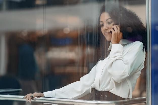 Młoda kobieta ze smartfonem wspina się szklaną windą