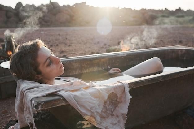 Młoda kobieta ze smutnym wzrokiem relaksuje się w brudnej kąpieli na pustyni