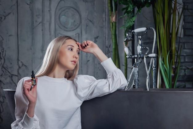 Młoda kobieta ze świeżą idealną skórą pozowanie o kąpieli w pokoju wnętrza łazienki z olejem. koncepcja kosmetologii i leczenia. koncepcje reklamowe zdrowego stylu życia, spa i samoopieki. skopiuj miejsce