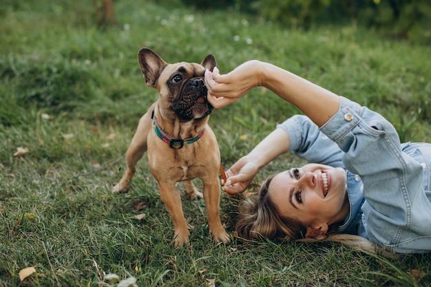 Młoda kobieta ze swoim zwierzakiem buldogiem francuskim w parku