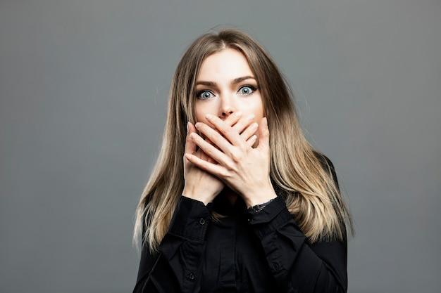 Młoda kobieta ze zgrozą zakryła usta dłońmi. piękna blondynka w czarnej koszuli. panika, stres i problemy. szare tło.