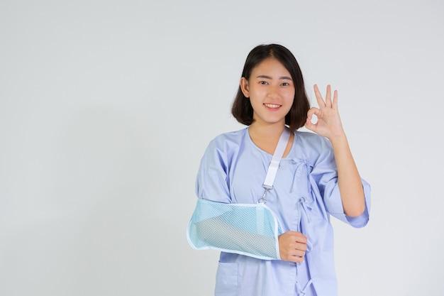 Młoda kobieta ze złamaną ręką nosząca szynę na ramię