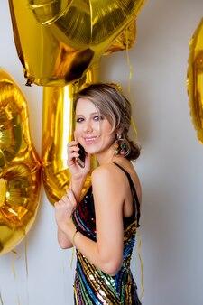 Młoda kobieta ze złotymi balonami na swoje trzydzieści lat urodziny i dzwoniąc do przyjaciół przez telefon komórkowy. osoba jest w sukience i fryzurze w stylu vintage z lat 80-tych.