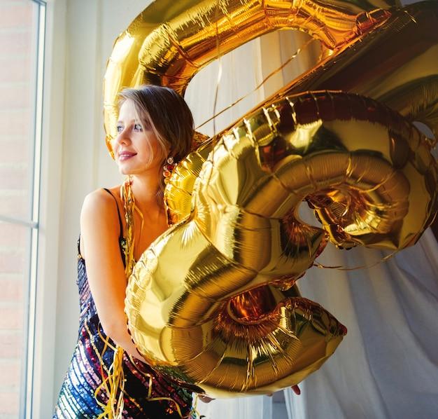 Młoda kobieta ze złotymi balonami w pobliżu okna. osoba jest w sukience i fryzurze w stylu vintage z lat 80-tych. w domu