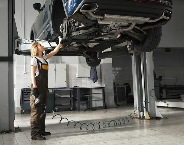 Młoda kobieta żeński mechanik sprawdza podwozie w warsztacie