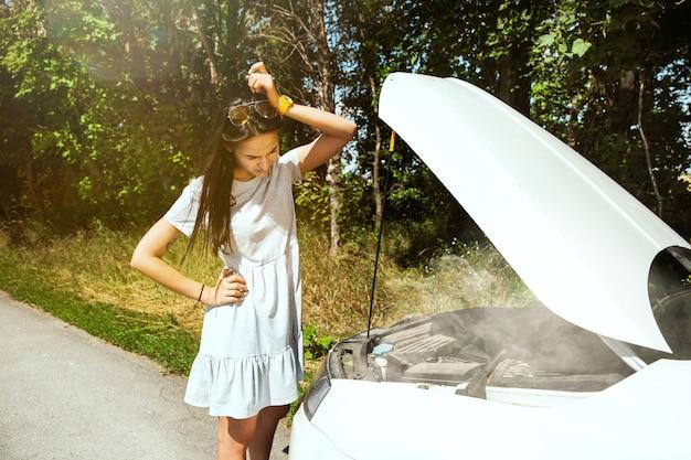 Młoda kobieta zepsuła samochód w drodze na odpoczynek. ona sama próbuje naprawić zepsute lub powinna autostopem. denerwowanie się. weekend, kłopoty w drodze, wakacje.