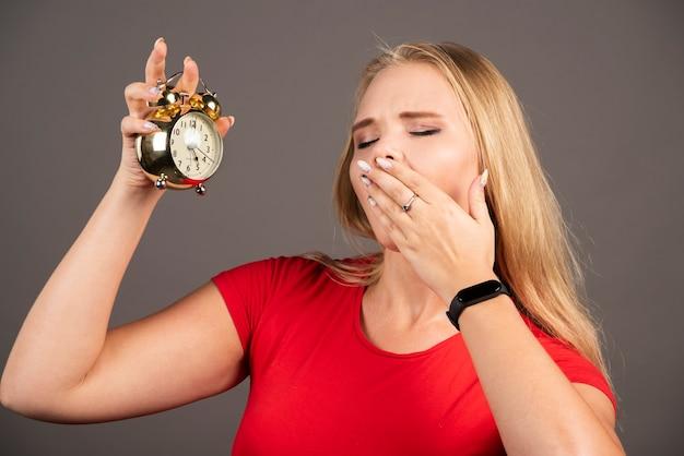 Młoda kobieta ziewanie na czarnej ścianie z zegarem.