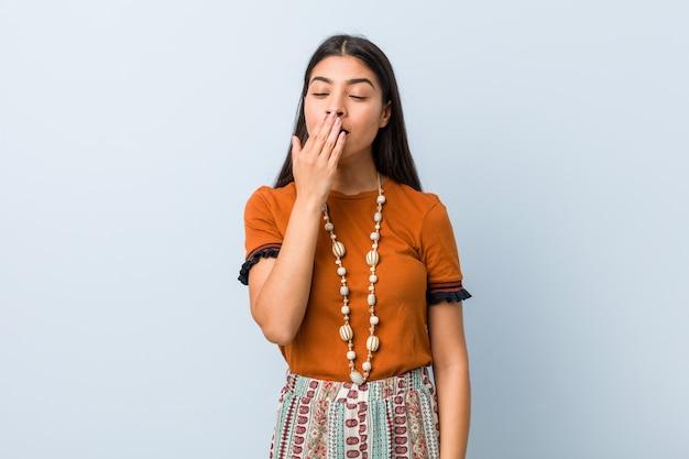Młoda kobieta ziewanie pokazując zmęczony gest obejmujący usta ręką