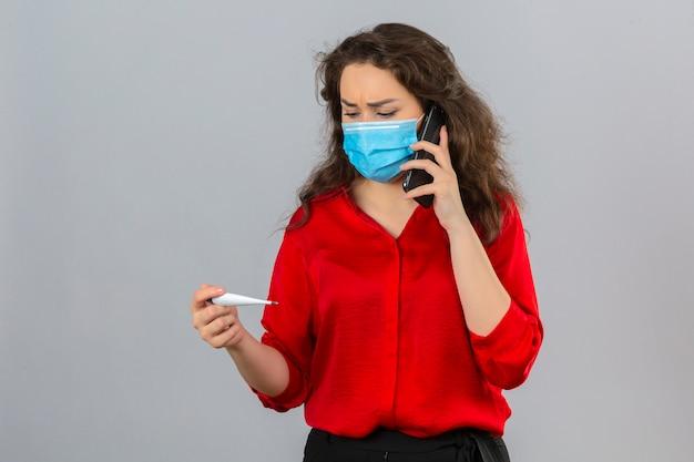 Młoda kobieta zmartwiona ubrana w czerwoną bluzkę w masce ochronnej medycznej rozmawia przez telefon komórkowy patrząc na cyfrowy termometr na białym tle