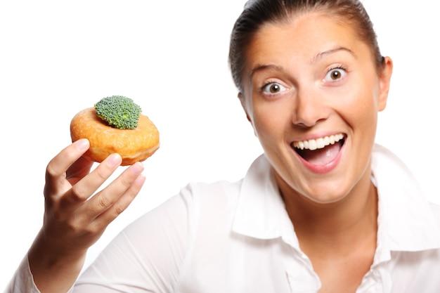 Młoda kobieta znajdująca idealny kompromis między jedzeniem pączka i brokułów