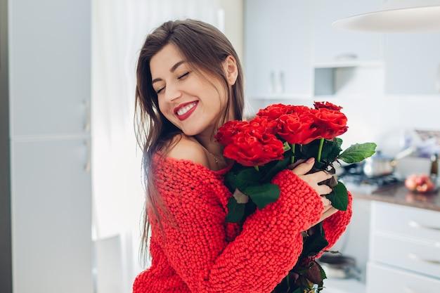 Młoda kobieta znalazła bukiet róż w kuchni. szczęśliwa dziewczyna trzyma i przytulanie kwiaty. niespodzianka na walentynki