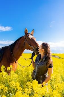 Młoda kobieta zostaje blisko brown konia w żółtym gwałta lub oleistego polu z niebieskim niebem