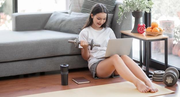Młoda kobieta zostaje w domu i uczy się treningu online w domu.