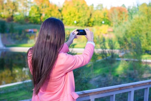 Młoda kobieta zrobić zdjęcie jej telefonem na jesienny dzień