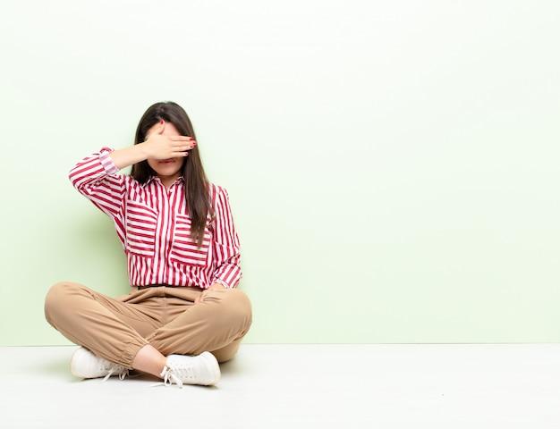 Młoda kobieta zwężająca oczy jedną ręką czująca się przestraszona lub niespokojna, zastanawiająca się lub na ślepo czekająca na niespodziankę siedząca na podłodze