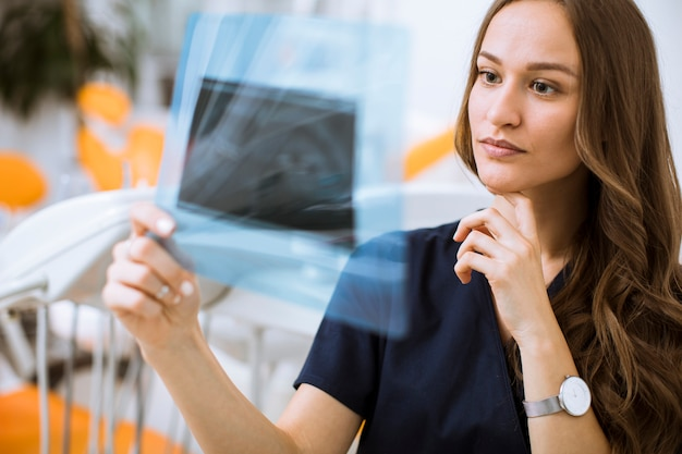 Młoda kobiety lekarka egzamininuje radiograph w dentysty biurze z rękawiczkami ochronnymi