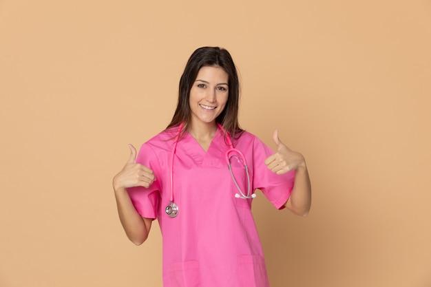 Młoda kobiety lekarka gestykuluje nad brąz ścianą z różowym mundurem
