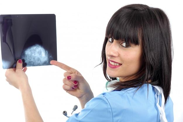 Młoda kobiety lekarka patrzeje pacjenta promieniowanie rentgenowskie z stetoskopem