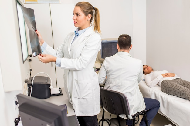 Młoda kobiety lekarka patrzeje promieniowanie rentgenowskie wizerunek pacjent w szpitalu