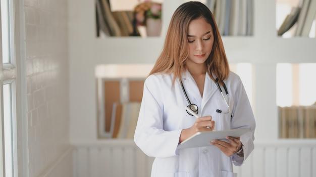 Młoda kobiety lekarka pracuje na dokumentacji medycznej i egzaminie wynika z pastylką