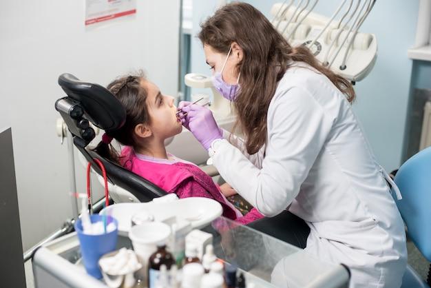 Młoda kobiety lekarka taktuje cierpliwych dziewczyna zęby przy stomatologicznym kliniki biurem. sprzęt dentystyczny