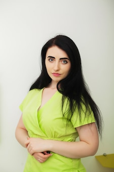 Młoda kobiety lekarka w zielonym żakiecie w stomatologicznym biurze
