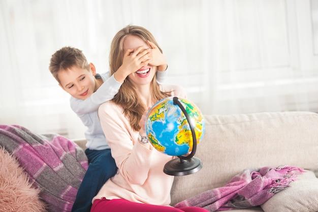 Młoda kochająca matka ma zabawę z jej dzieckiem indoors. ładna mama i jej synek bawiące się w domu ze światem decydującym, gdzie podróżować